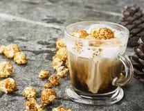一杯与乳脂状的泡沫的味道好的鲜乳咖啡冠上了用在一块灰色石头的焦糖酥脆玉米花 免版税库存图片