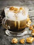 一杯与乳脂状的泡沫的味道好的鲜乳咖啡冠上了用在一块灰色石头的焦糖酥脆玉米花 免版税图库摄影