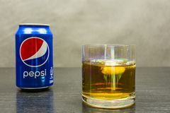 一杯与冰和一个罐头的威士忌酒百事可乐 库存图片