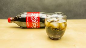 一杯与冰块的可口可乐 瓶在背景中 免版税图库摄影