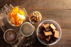一杯与各种各样的快餐的淡和黑啤酒对在棕色木背景的啤酒 图库摄影