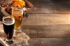一杯与各种各样的快餐的淡和黑啤酒对在棕色背景的啤酒 免版税库存照片