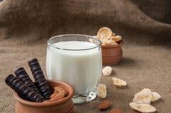 一杯与杏仁坚果,玉米片,巧克力的牛奶,在袋装的粗麻布背景 库存图片
