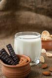 一杯与杏仁坚果,玉米片,巧克力的牛奶,在袋装的粗麻布背景 免版税图库摄影