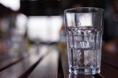 一杯与水下落的冰在它附近凝聚 免版税库存图片