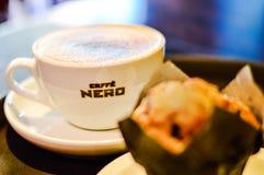 一杯从Caffe尼罗的热奶咖啡用松饼 免版税库存图片