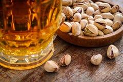 一杯低度黄啤酒和几个开心果在木ta 免版税库存图片