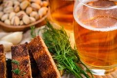 一杯低度黄啤酒和快餐,黑麦面包干用在woode的莳萝 免版税库存图片