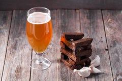 一杯低度黄啤酒和bl油煎的热的芳香大蒜多士  库存照片