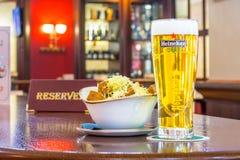 一杯低度黄啤酒海涅肯用面包干乳酪,片剂-是后备的在餐馆酒吧的一张木桌上 俄国 莫斯科 免版税图库摄影