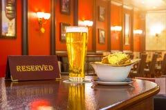 一杯低度黄啤酒用面包干乳酪,片剂-是后备的在餐馆酒吧的一张木桌上 库存照片