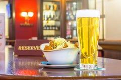 一杯低度黄啤酒用面包干乳酪,片剂-是后备的在餐馆酒吧的一张木桌上 免版税库存图片