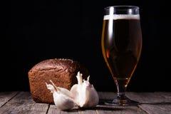 一杯低度黄啤酒,黑面包大面包和大蒜在t说谎 库存图片