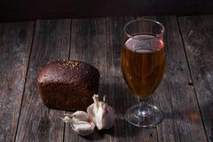 一杯低度黄啤酒,黑面包大面包和大蒜在t说谎 免版税库存图片