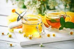 一杯健康茶,一个瓶子蜂蜜和花 选择聚焦 免版税库存图片