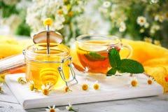 一杯健康茶,一个瓶子蜂蜜和花 选择聚焦 图库摄影