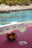 一杯冷的白酒和一碗樱桃和杏子在游艇桌上在离Agistri海岛的附近,萨龙湾海岸, 库存图片