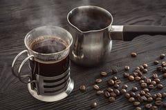 一杯咖啡、一个咖啡罐和咖啡豆在棕色背景 免版税库存照片