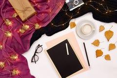 一杯咖啡、一个小黑木板和白色白垩与新年目标 在白色的围巾和圣诞灯 库存图片