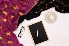 一杯咖啡、一个小黑木板和白色白垩与新年目标 在白色的围巾和圣诞灯 免版税库存照片