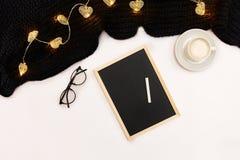 一杯咖啡、一个小黑木板和白色白垩与新年目标 在白色的围巾和圣诞灯 免版税库存图片