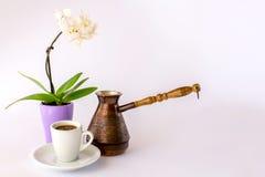 一杯咖啡、一朵白色兰花和cezve 免版税库存照片