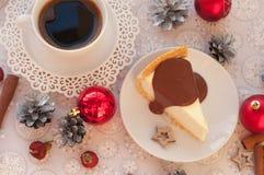一杯咖啡、开胃乳酪蛋糕的片断用对此的熔化巧克力,银色锥体、肉桂条和圣诞节t 免版税库存照片