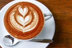 一杯咖啡与心脏样式的在木后面的一个白色杯子 库存照片