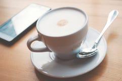 一杯咖啡与泡沫的和在桌上的一个智能手机 免版税库存照片