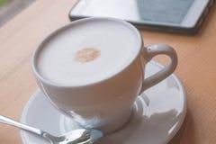 一杯咖啡与泡沫的和在桌上的一个智能手机 免版税库存图片