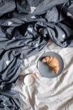 一杯咖啡和一个新月形面包在一块板材在一张舒适床上 免版税库存照片