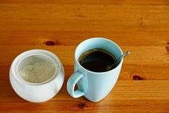 一杯咖啡和一个糖罐用糖在一张木桌上 图库摄影