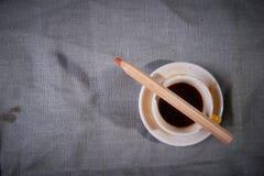 一杯咖啡和一支铅笔在灰色背景 免版税图库摄影