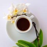 一杯咖啡和一朵小白色兰花在板材 图库摄影