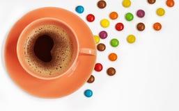 一杯咖啡和五颜六色的糖果在白色背景 免版税库存图片