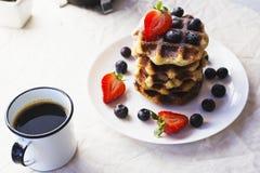 一杯咖啡和奶蛋烘饼和莓果板材  免版税库存图片