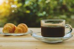 一杯咖啡和新月形面包在被弄脏的绿色自然本底 库存照片