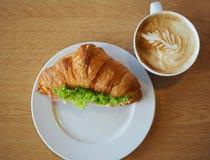 一杯咖啡和新月形面包火腿乳酪三明治 免版税库存照片