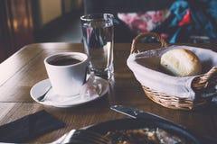 一杯咖啡和早餐在一个舒适减速火箭的样式咖啡馆 免版税库存照片
