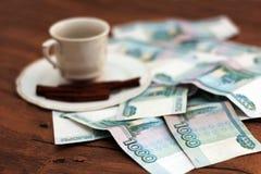 一杯咖啡和金钱 免版税库存照片