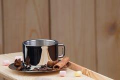 一杯咖啡在一个木架子的,用桂香、茴香、咖啡豆和蛋白软糖 免版税库存照片