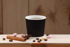 一杯咖啡在一个木架子的,用桂香、茴香、咖啡豆和蛋白软糖 免版税图库摄影