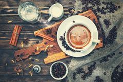 一杯咖啡在一张土气木桌用香料,桂香,牛奶,水,盐,咖啡豆上的 定调子 免版税库存照片