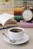 一杯咖啡在一张桌上的在书中 免版税库存图片