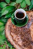 一杯咖啡在一棵砍的树的与咖啡豆和叶子 免版税库存图片