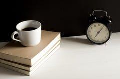 一杯咖啡在上面的与减速火箭的闹钟的书 免版税库存照片