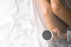 一杯咖啡在他们的手上在一条白色毯子的床,简单,家庭,在框架拷贝空间顶视图白光设色的空间上 免版税库存照片