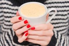一杯咖啡在妇女的手上 免版税库存照片
