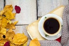 一杯咖啡在木桌上的与下落的叶子 图库摄影