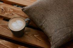 一杯咖啡在木背景与一个灰色枕头,咖啡时间的 免版税库存照片